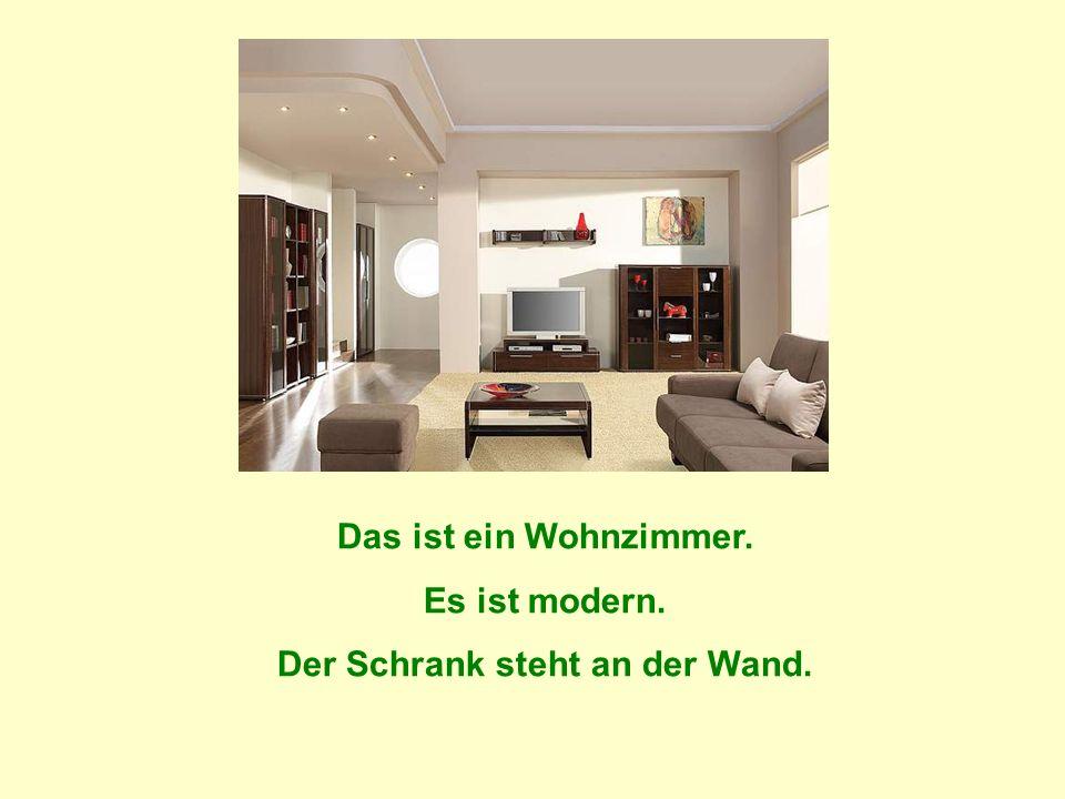 Das ist ein Wohnzimmer. Es ist modern. Der Schrank steht an der Wand.
