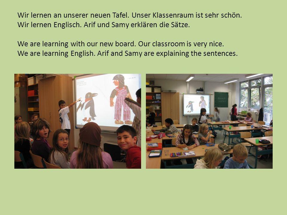 Wir lernen an unserer neuen Tafel. Unser Klassenraum ist sehr schön. Wir lernen Englisch. Arif und Samy erklären die Sätze. We are learning with our n