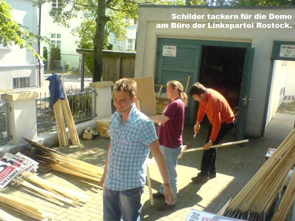 Schilder tackern für die Demo am Büro der Linkspartei Rostock.