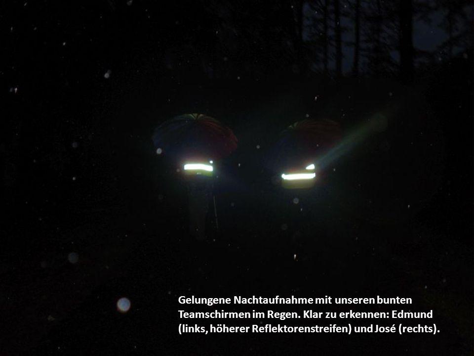 Gelungene Nachtaufnahme mit unseren bunten Teamschirmen im Regen. Klar zu erkennen: Edmund (links, höherer Reflektorenstreifen) und José (rechts).