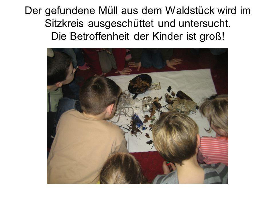 Der gefundene Müll aus dem Waldstück wird im Sitzkreis ausgeschüttet und untersucht. Die Betroffenheit der Kinder ist groß!