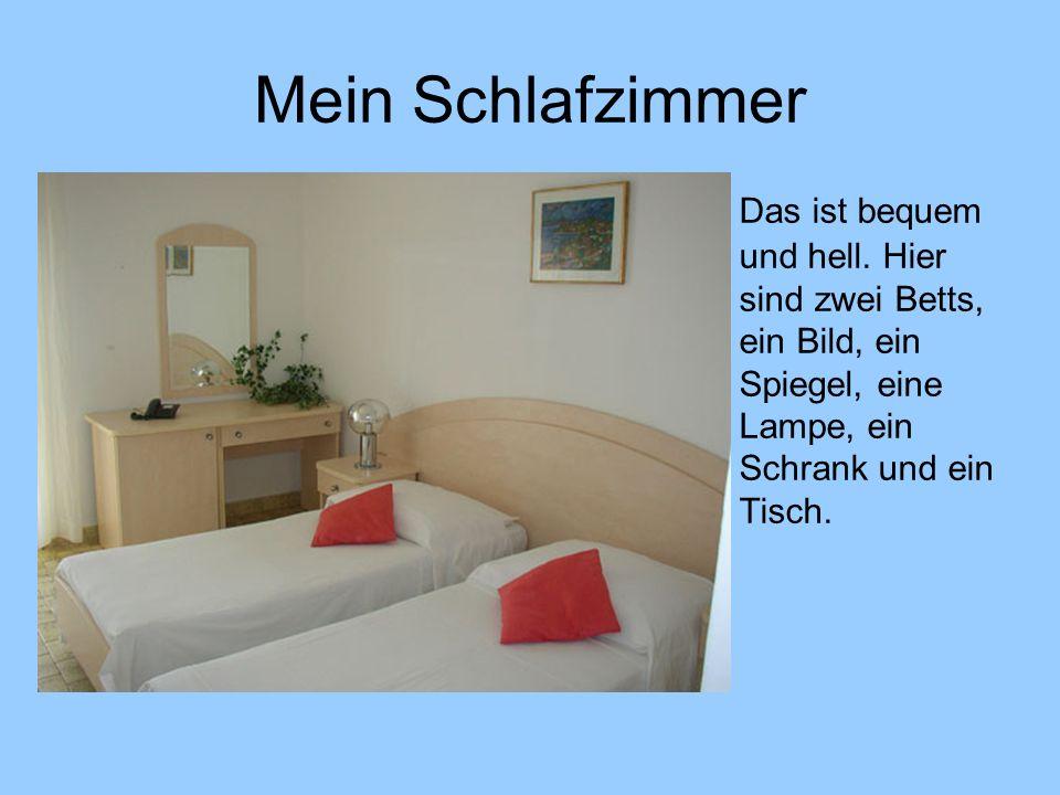 Mein Schlafzimmer Das ist bequem und hell. Hier sind zwei Betts, ein Bild, ein Spiegel, eine Lampe, ein Schrank und ein Tisch.