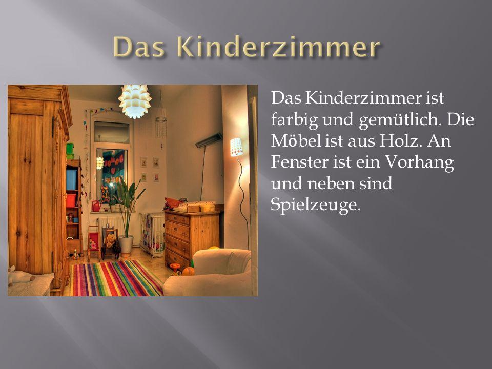 Das Kinderzimmer ist farbig und gemütlich. Die M ӧ bel ist aus Holz. An Fenster ist ein Vorhang und neben sind Spielzeuge.