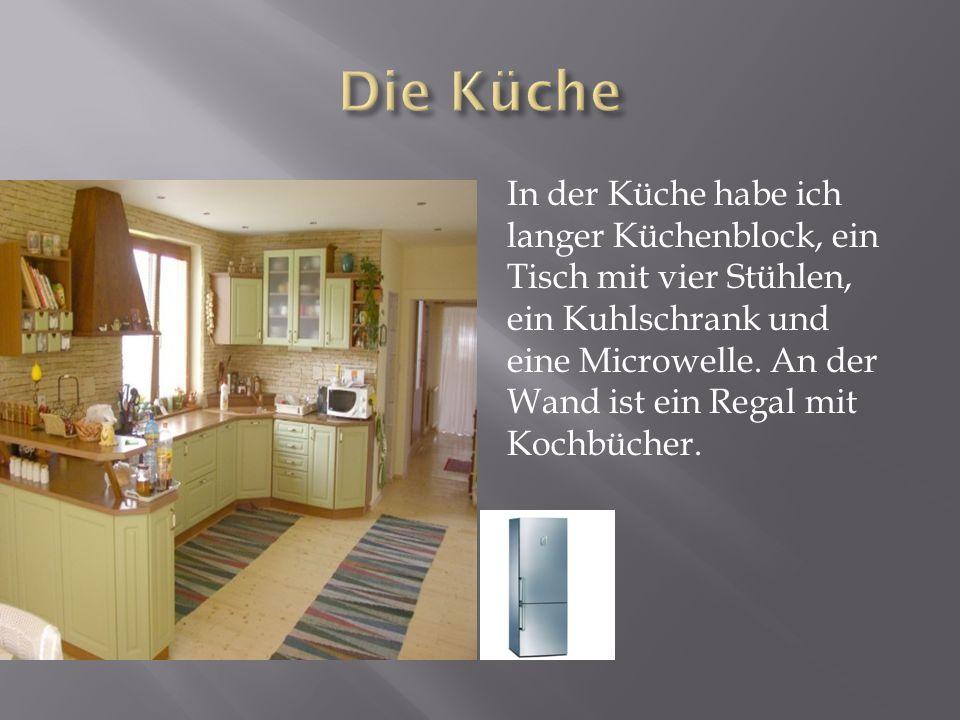 In der Küche habe ich langer Küchenblock, ein Tisch mit vier Stühlen, ein Kuhlschrank und eine Microwelle. An der Wand ist ein Regal mit Kochbücher.