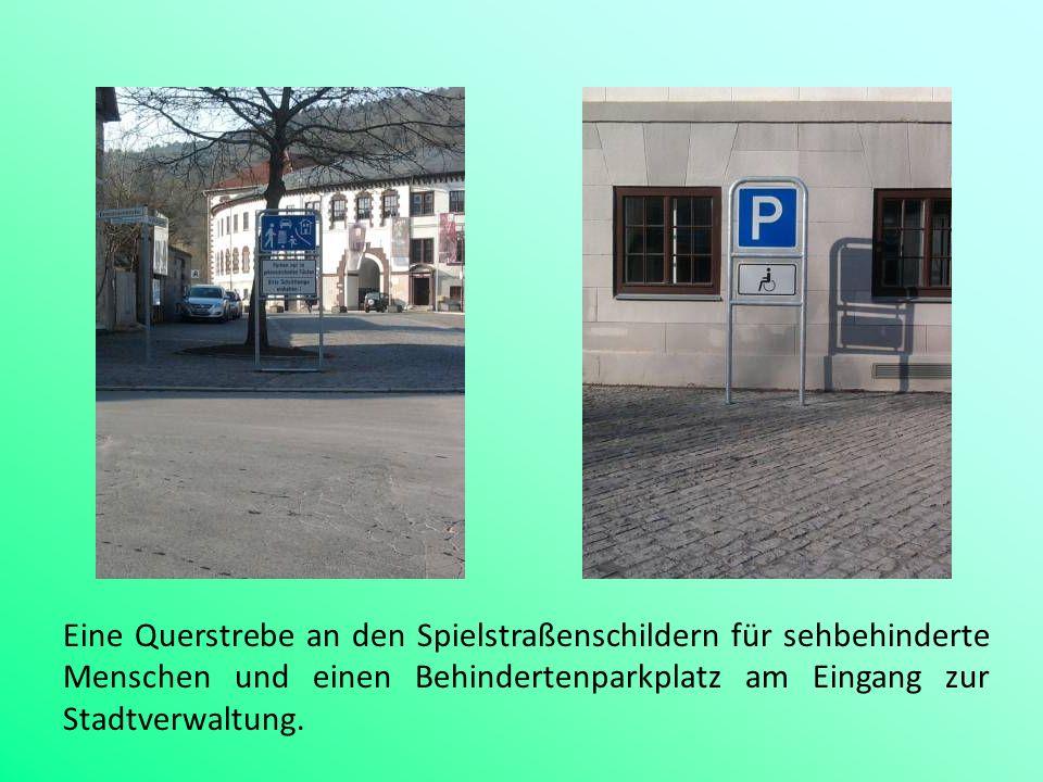 Eine Querstrebe an den Spielstraßenschildern für sehbehinderte Menschen und einen Behindertenparkplatz am Eingang zur Stadtverwaltung.