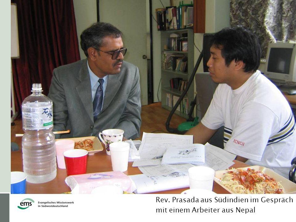 Rev. Prasada aus Südindien im Gespräch mit einem Arbeiter aus Nepal
