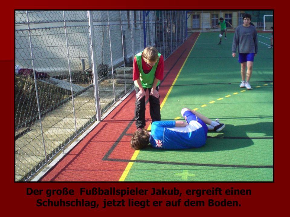 Der große Fußballspieler Jakub, ergreift einen Schuhschlag, jetzt liegt er auf dem Boden.