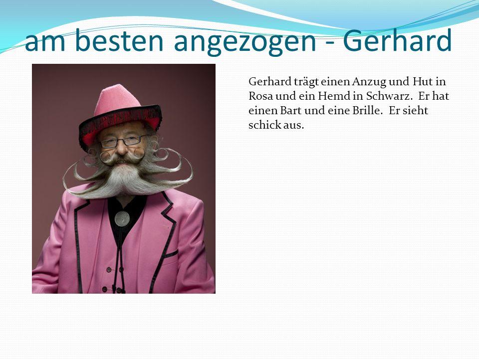 am besten angezogen - Gerhard Gerhard trägt einen Anzug und Hut in Rosa und ein Hemd in Schwarz.