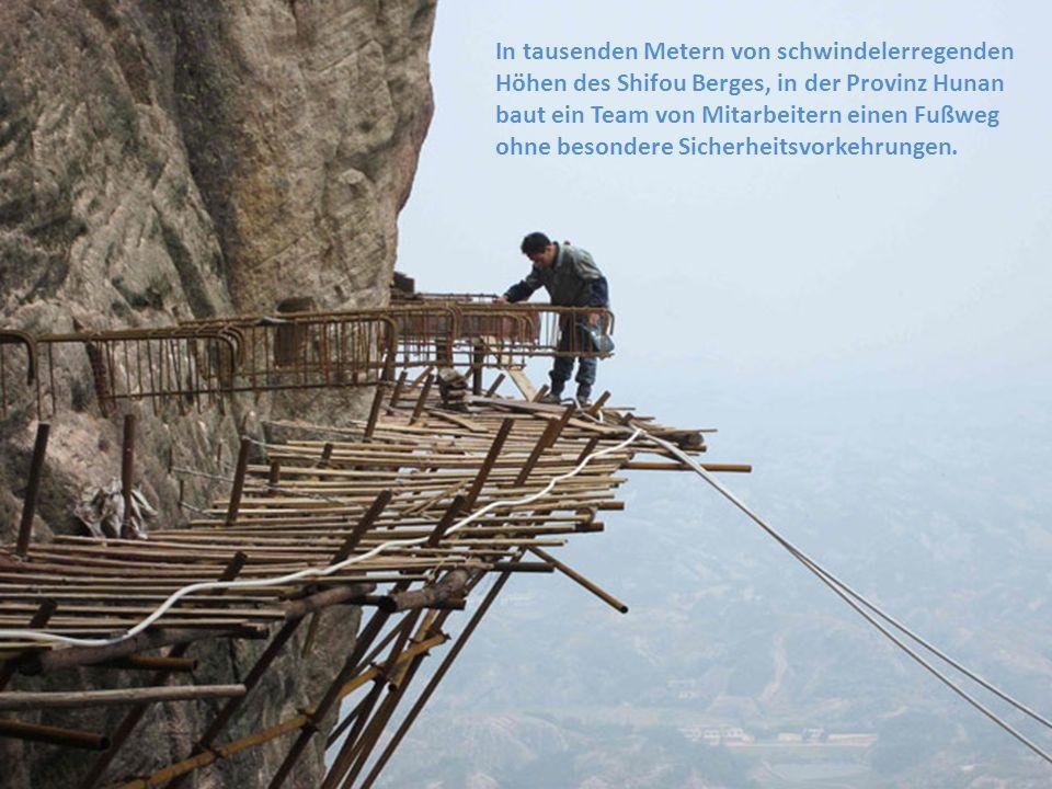 In tausenden Metern von schwindelerregenden Höhen des Shifou Berges, in der Provinz Hunan baut ein Team von Mitarbeitern einen Fußweg ohne besondere S