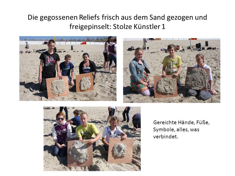 Die gegossenen Reliefs frisch aus dem Sand gezogen und freigepinselt: Stolze Künstler 1 Gereichte Hände, Füße, Symbole, alles, was verbindet.