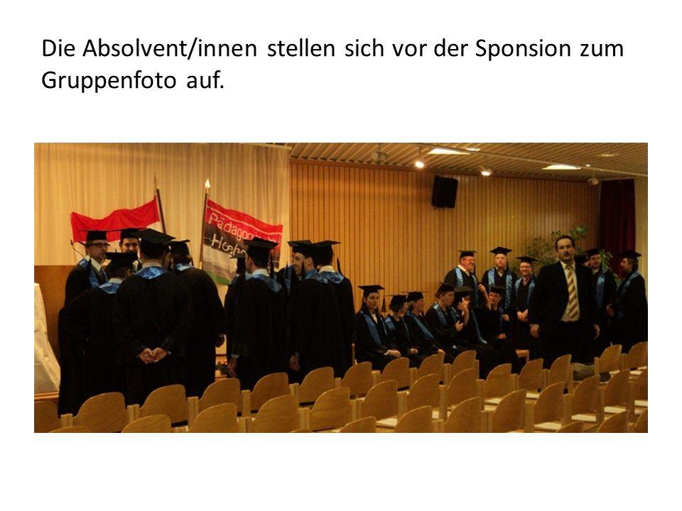 Die Absolvent/innen stellen sich vor der Sponsion zum Gruppenfoto auf.