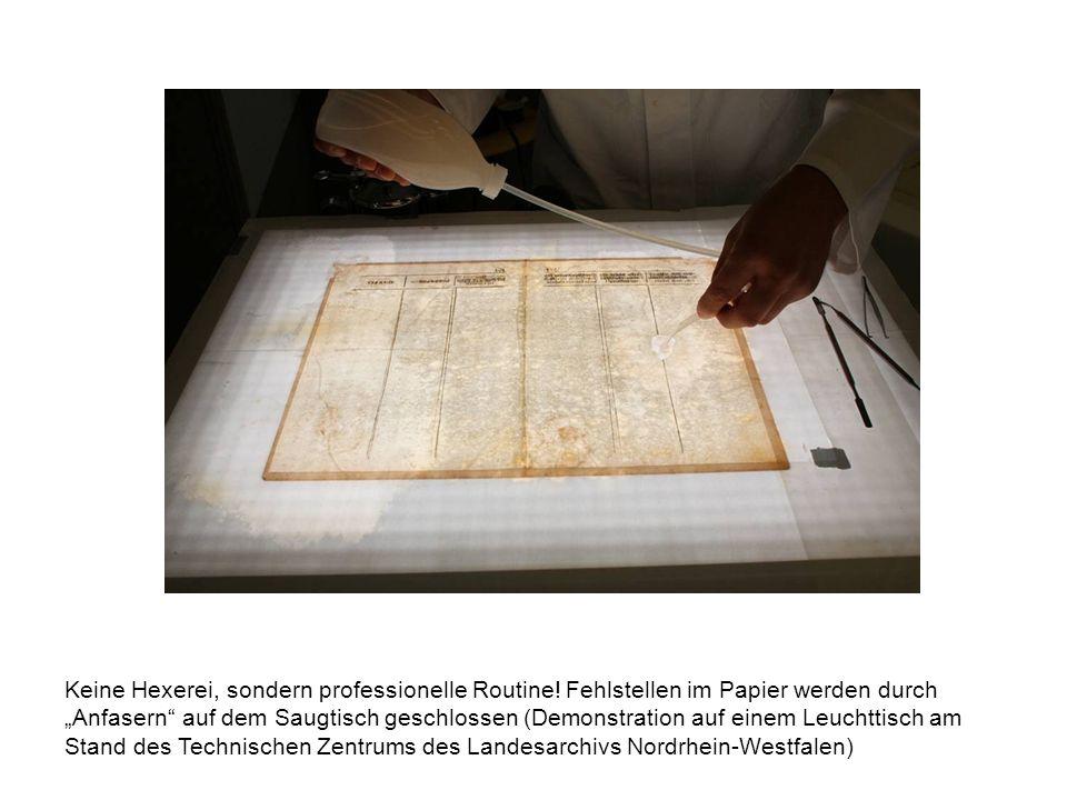 Keine Hexerei, sondern professionelle Routine! Fehlstellen im Papier werden durch Anfasern auf dem Saugtisch geschlossen (Demonstration auf einem Leuc
