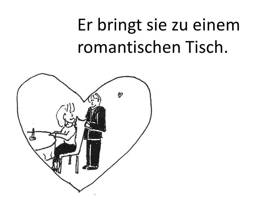 Er bringt sie zu einem romantischen Tisch.
