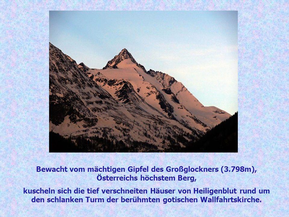 Bewacht vom mächtigen Gipfel des Großglockners (3.798m), Österreichs höchstem Berg, kuscheln sich die tief verschneiten Häuser von Heiligenblut rund u