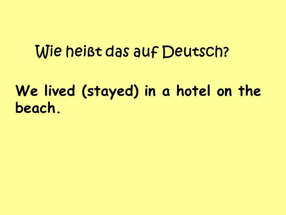 Wie heißt das auf Deutsch We lived (stayed) in a hotel on the beach.