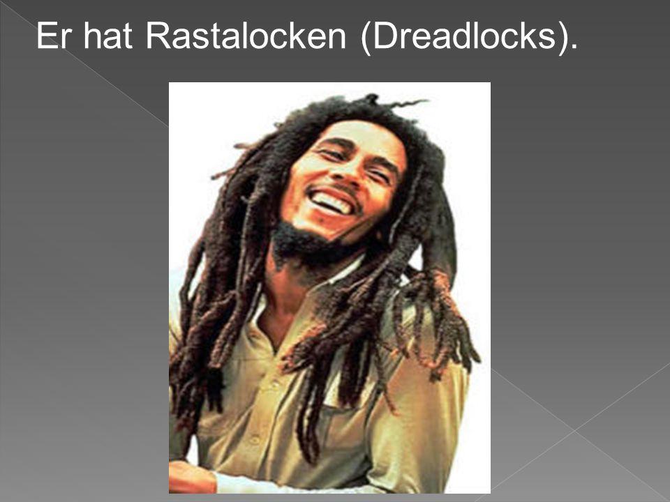 Er hat Rastalocken (Dreadlocks).