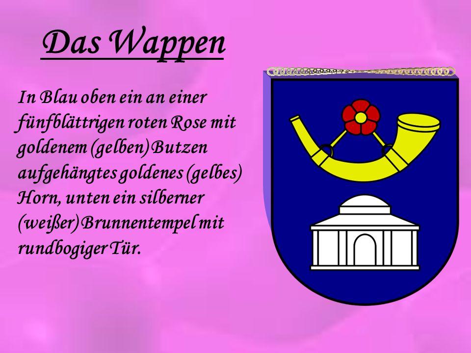 Das Wappen In Blau oben ein an einer fünfblättrigen roten Rose mit goldenem (gelben) Butzen aufgehängtes goldenes (gelbes) Horn, unten ein silberner (