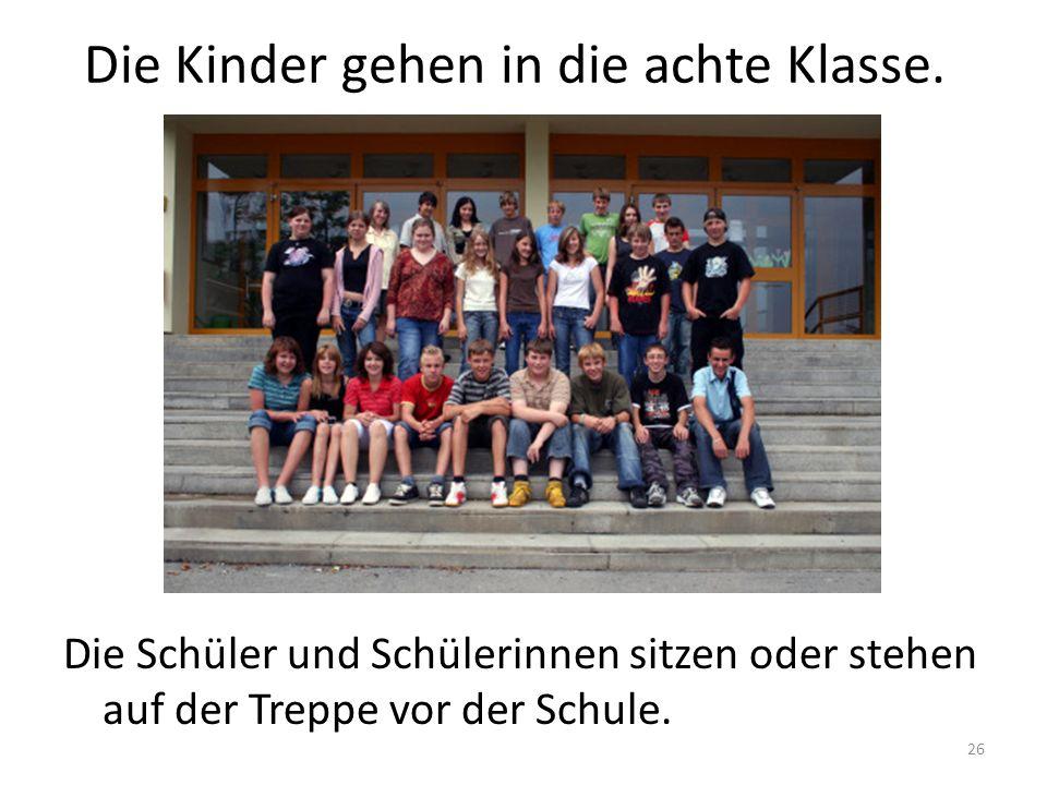 26 Die Kinder gehen in die achte Klasse. Die Schüler und Schülerinnen sitzen oder stehen auf der Treppe vor der Schule.
