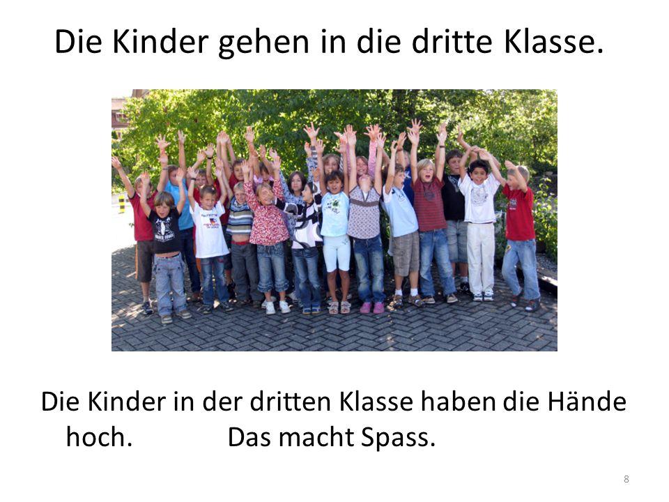 8 Die Kinder gehen in die dritte Klasse. Die Kinder in der dritten Klasse haben die Hände hoch. Das macht Spass.