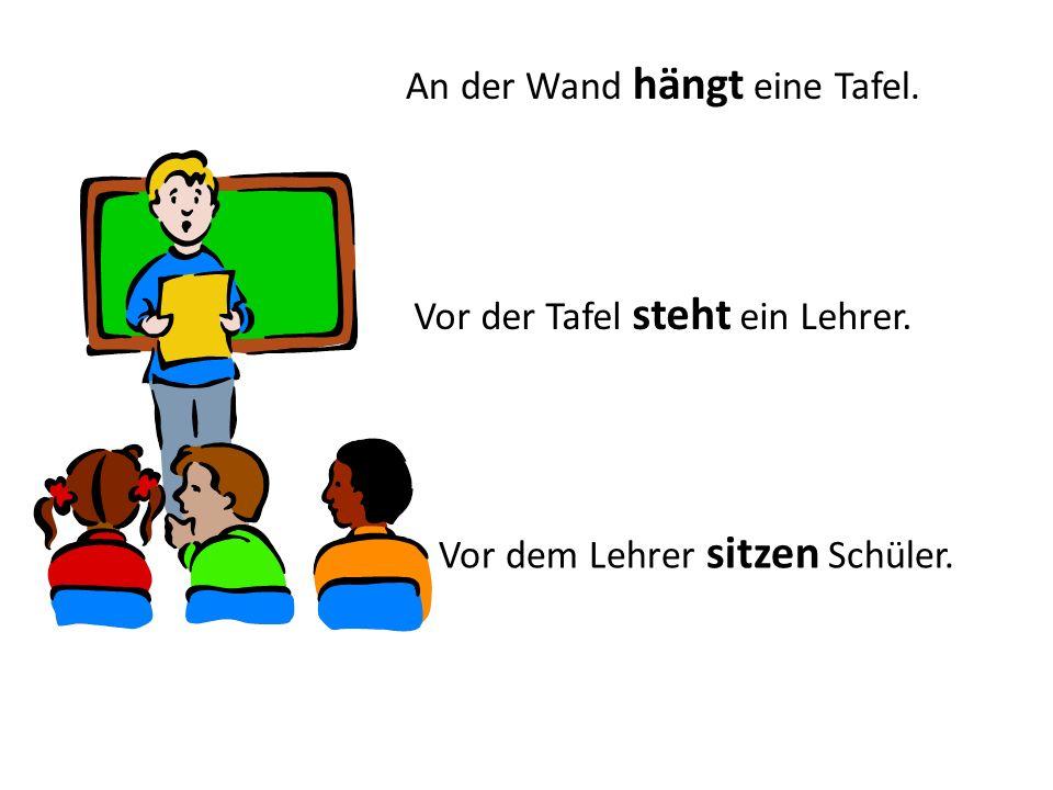 An der Wand hängt eine Tafel. Vor der Tafel steht ein Lehrer. Vor dem Lehrer sitzen Schüler.