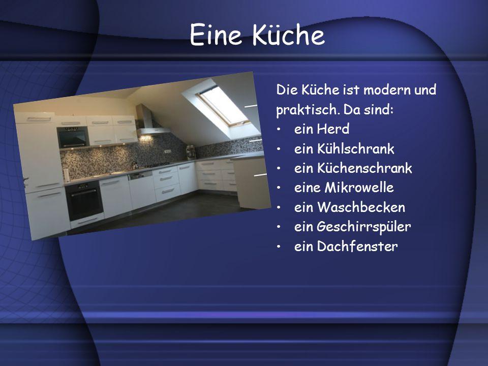 Eine Küche Die Küche ist modern und praktisch. Da sind: ein Herd ein Kühlschrank ein Küchenschrank eine Mikrowelle ein Waschbecken ein Geschirrspüler