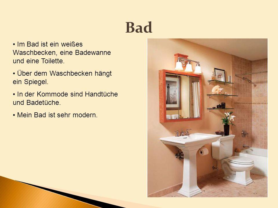 Bad Im Bad ist ein weißes Waschbecken, eine Badewanne und eine Toilette. Über dem Waschbecken hängt ein Spiegel. In der Kommode sind Handtüche und Bad