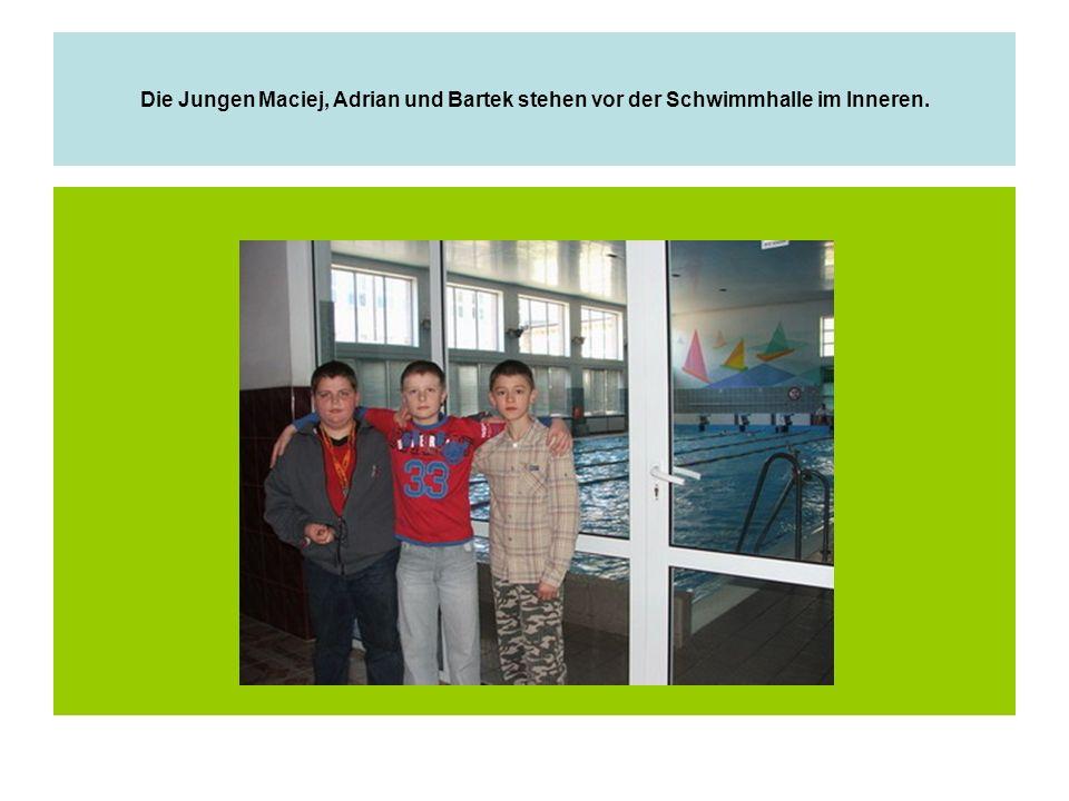 Die Jungen Maciej, Adrian und Bartek stehen vor der Schwimmhalle im Inneren.