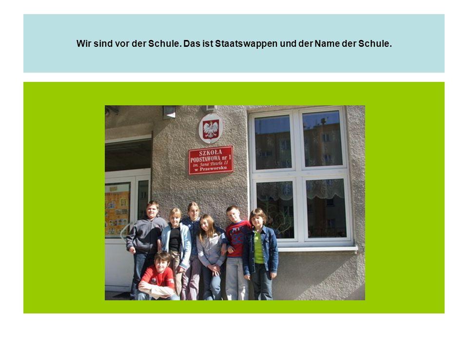 Wir sind vor der Schule. Das ist Staatswappen und der Name der Schule.