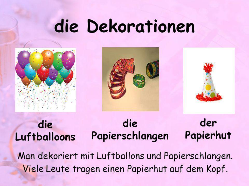 die Dekorationen Man dekoriert mit Luftballons und Papierschlangen. Viele Leute tragen einen Papierhut auf dem Kopf. die Luftballoons die Papierschlan