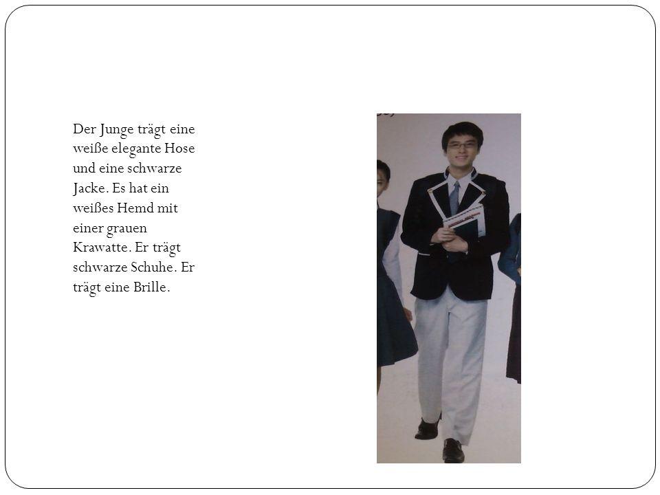 Der Junge trägt eine weiße elegante Hose und eine schwarze Jacke.