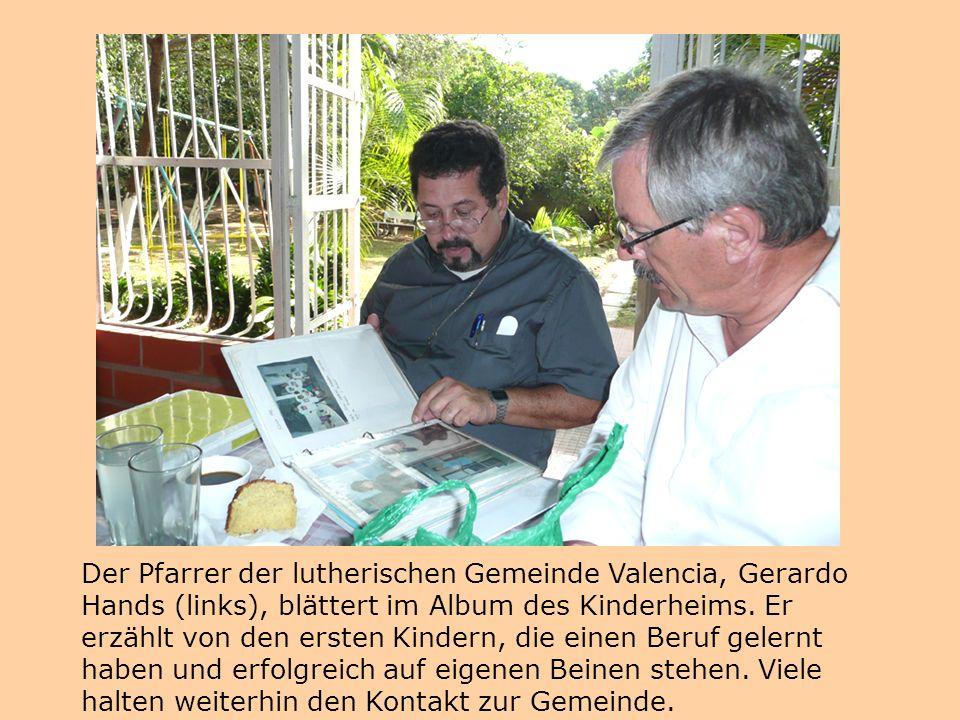 Der Pfarrer der lutherischen Gemeinde Valencia, Gerardo Hands (links), blättert im Album des Kinderheims.