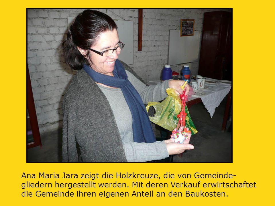 Ana Maria Jara zeigt die Holzkreuze, die von Gemeinde- gliedern hergestellt werden.