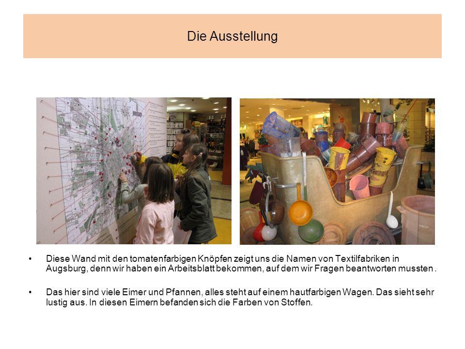 Die Ausstellung Diese Wand mit den tomatenfarbigen Knöpfen zeigt uns die Namen von Textilfabriken in Augsburg, denn wir haben ein Arbeitsblatt bekommen, auf dem wir Fragen beantworten mussten.
