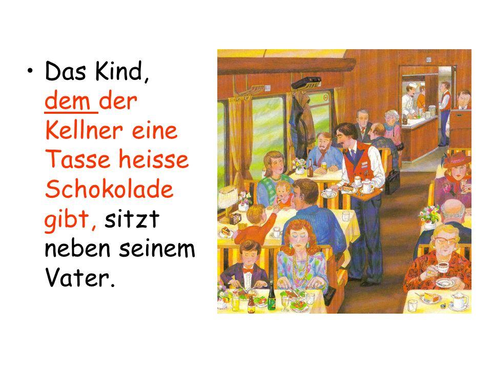 Das Kind, dem der Kellner eine Tasse heisse Schokolade gibt, sitzt neben seinem Vater.