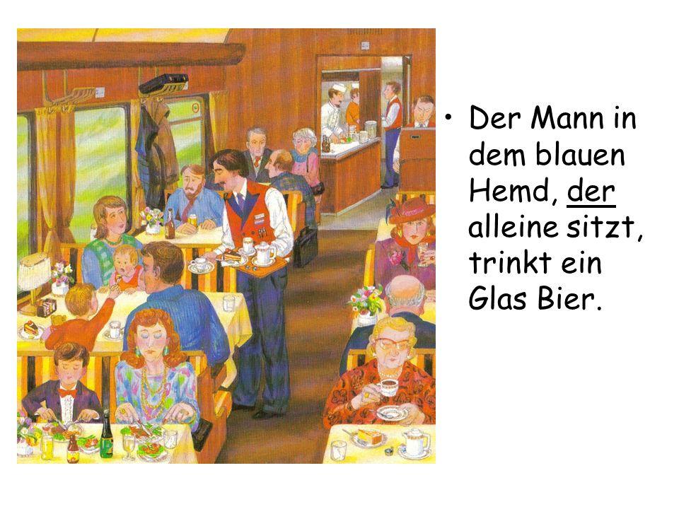 Der Mann in dem blauen Hemd, der alleine sitzt, trinkt ein Glas Bier.