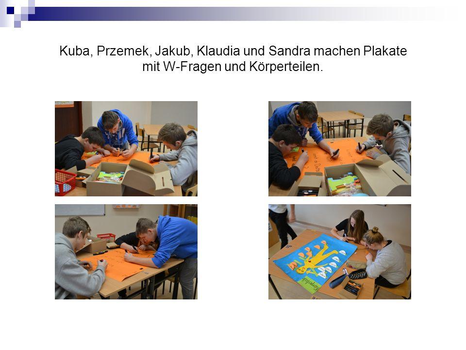 Kuba, Przemek, Jakub, Klaudia und Sandra machen Plakate mit W-Fragen und Körperteilen.