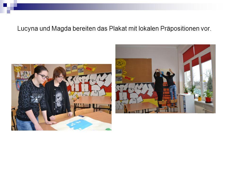 Lucyna und Magda bereiten das Plakat mit lokalen Präpositionen vor.