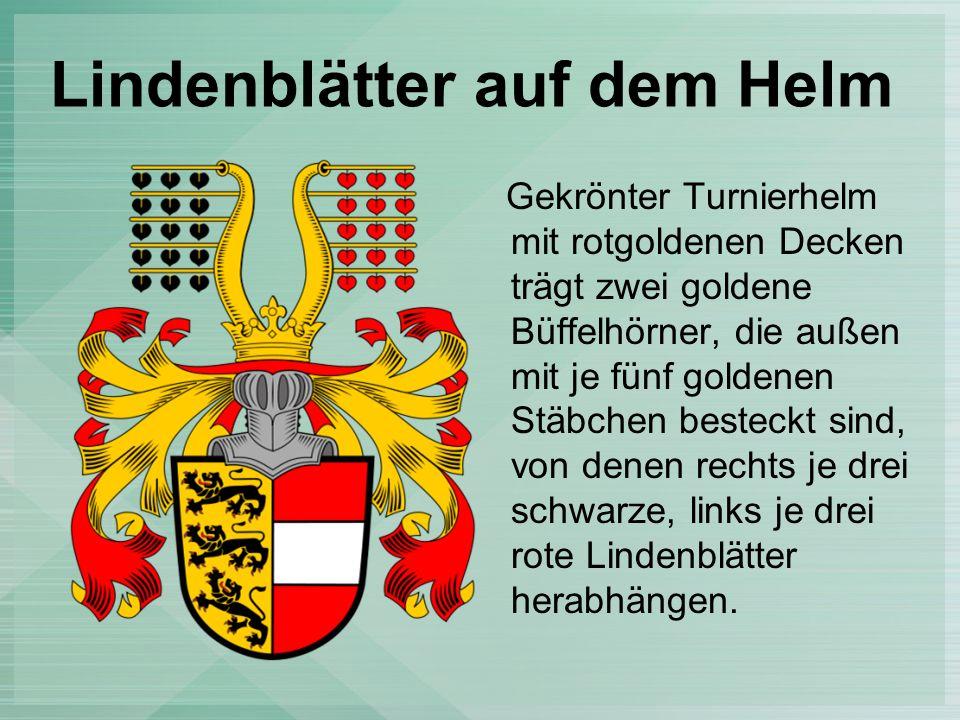 Lindenblätter auf dem Helm Gekrönter Turnierhelm mit rotgoldenen Decken trägt zwei goldene Büffelhörner, die außen mit je fünf goldenen Stäbchen besteckt sind, von denen rechts je drei schwarze, links je drei rote Lindenblätter herabhängen.