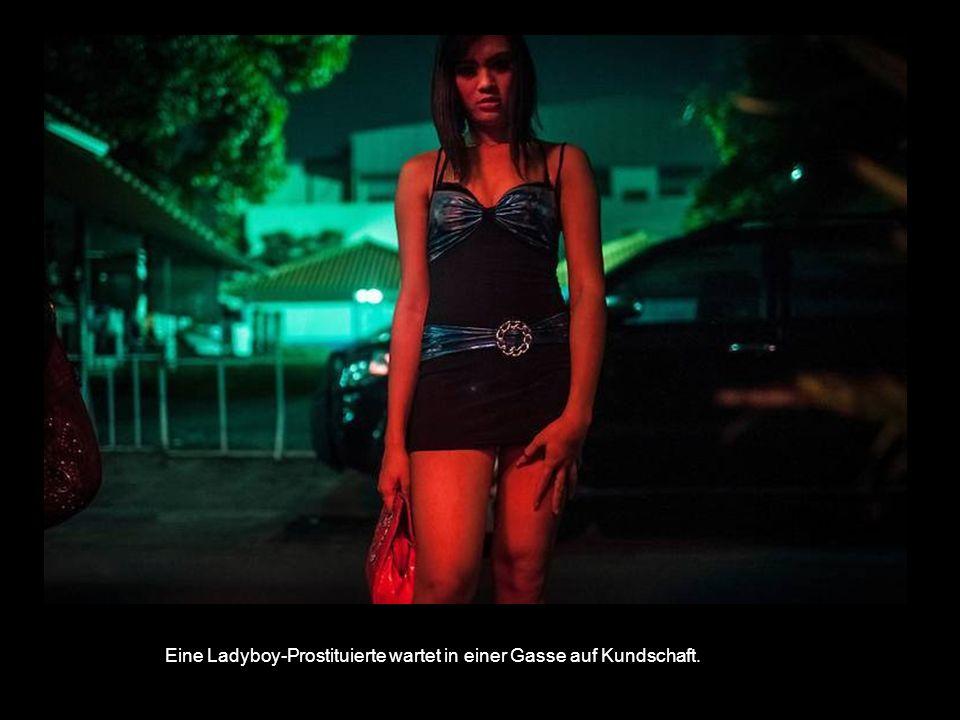 Eine Ladyboy-Prostituierte wartet in einer Gasse auf Kundschaft.