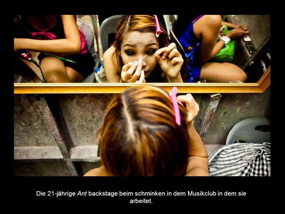 Die 21-jährige Ant backstage beim schminken in dem Musikclub in dem sie arbeitet.