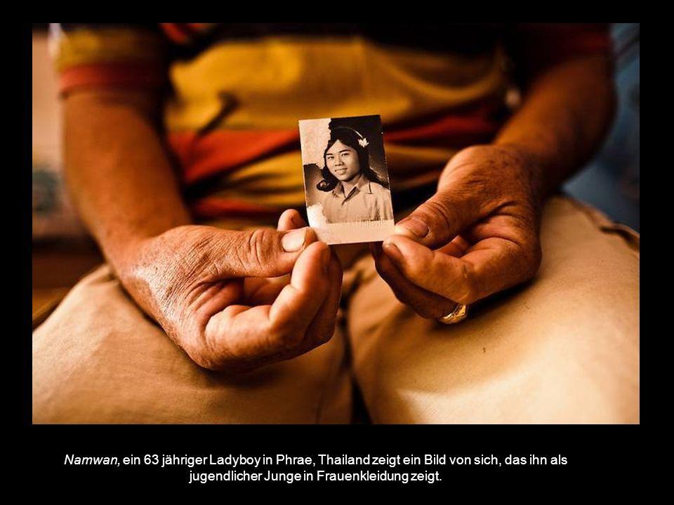 Namwan, ein 63 jähriger Ladyboy in Phrae, Thailand zeigt ein Bild von sich, das ihn als jugendlicher Junge in Frauenkleidung zeigt.