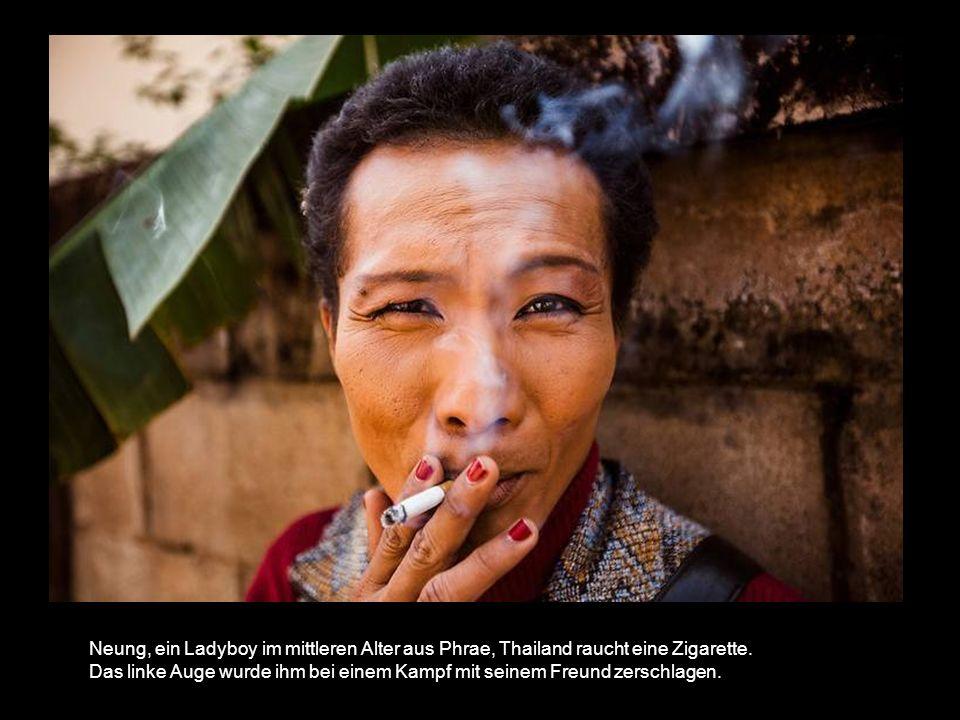 Neung, ein Ladyboy im mittleren Alter aus Phrae, Thailand raucht eine Zigarette.