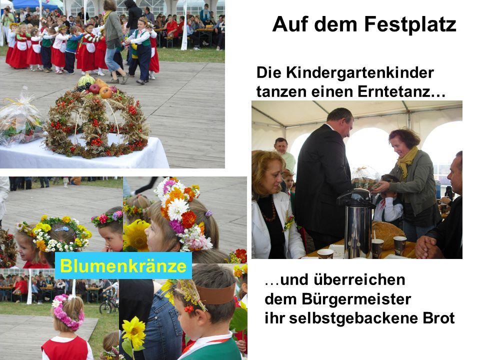 Auf dem Festplatz Die Kindergartenkinder tanzen einen Erntetanz… …und überreichen dem Bürgermeister ihr selbstgebackene Brot Blumenkränze