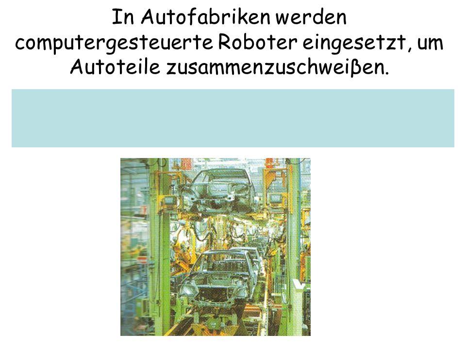 In Autofabriken werden computergesteuerte Roboter eingesetzt, um Autoteile zusammenzuschweiβen.