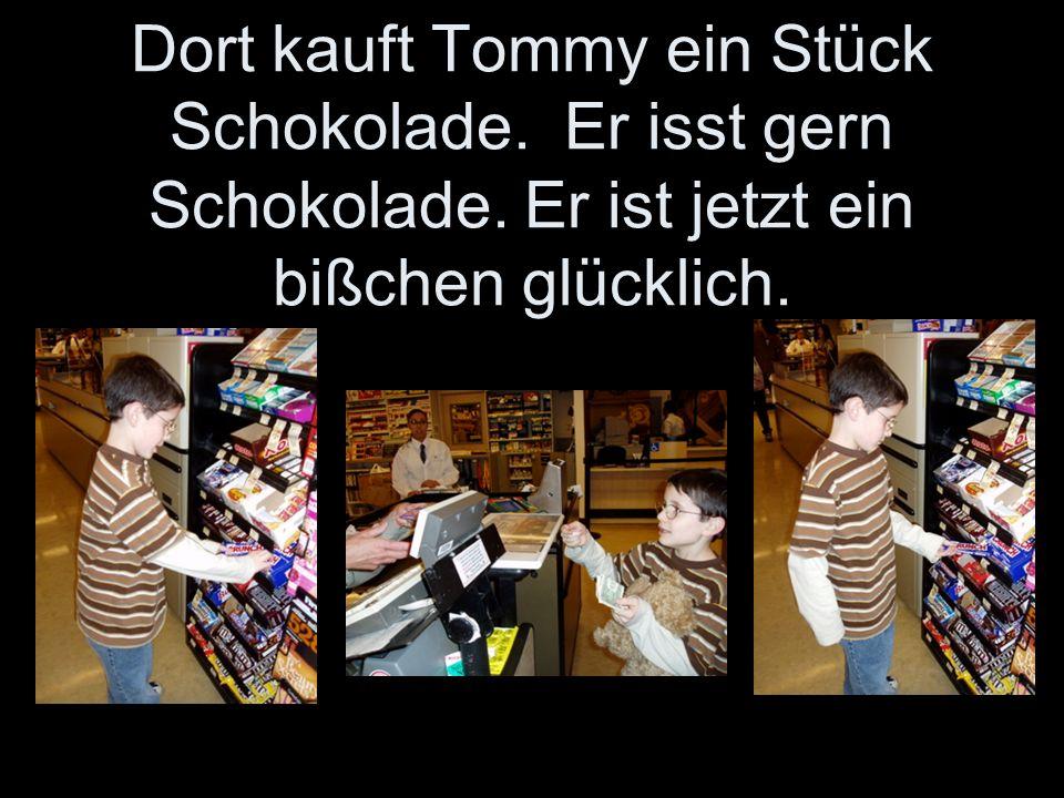 Dort kauft Tommy ein Stück Schokolade. Er isst gern Schokolade. Er ist jetzt ein bißchen glücklich.