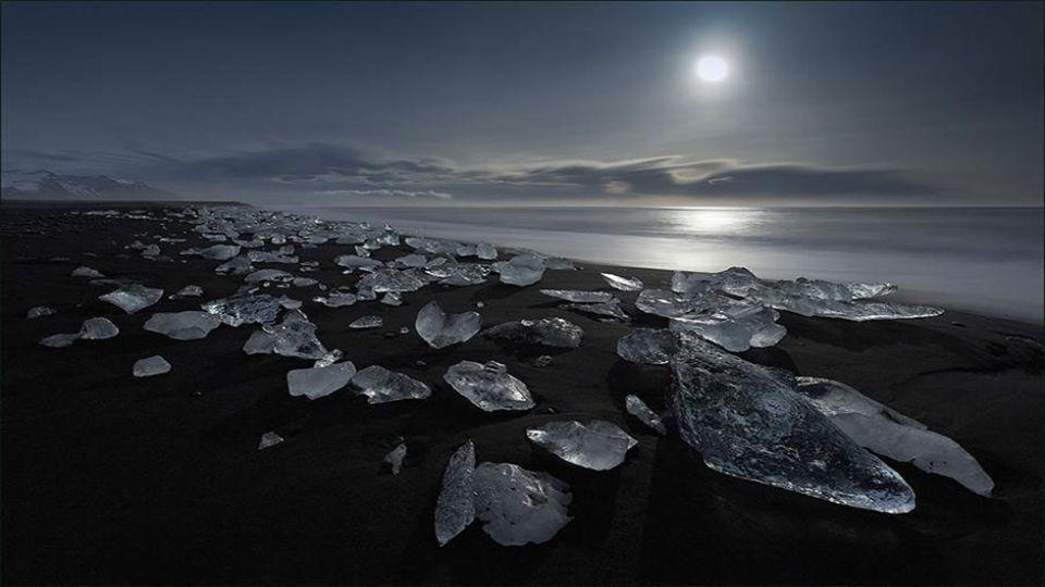 Der Strand von schwarzen vulkanischen Sand kontrastiert mit Stücken von weißem und glasigen Eis.