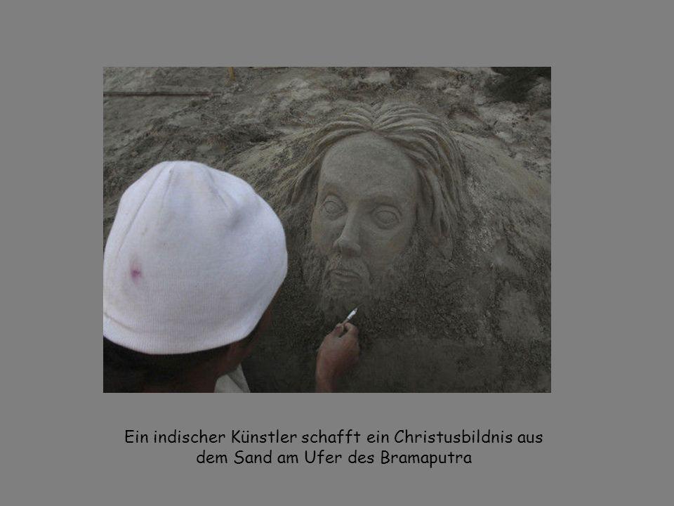 Ein indischer Künstler schafft ein Christusbildnis aus dem Sand am Ufer des Bramaputra