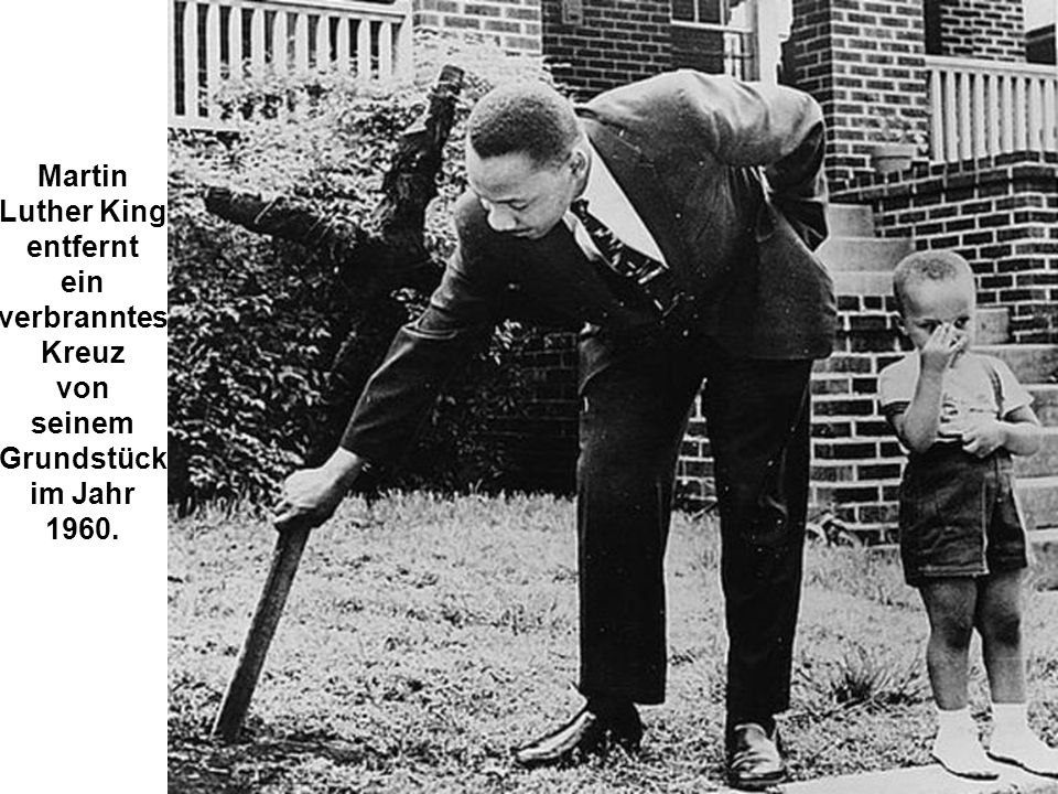 Martin Luther King entfernt ein verbranntes Kreuz von seinem Grundstück  im Jahr 1960.