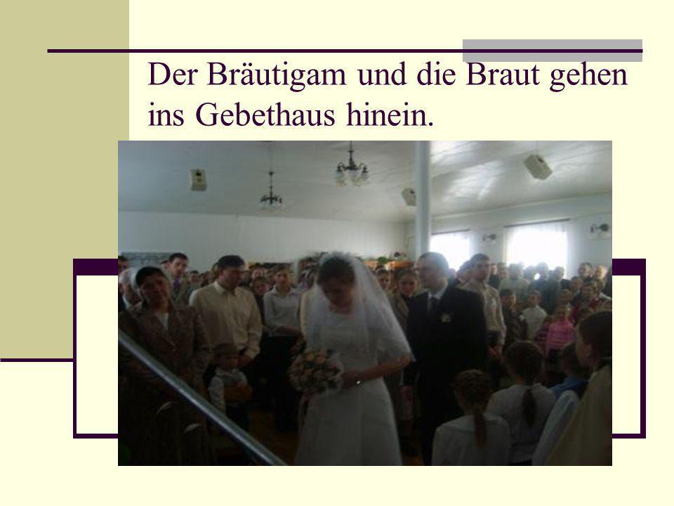 Der Bräutigam und die Braut gehen ins Gebethaus hinein.