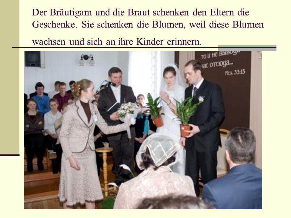 Der Bräutigam und die Braut schenken den Eltern die Geschenke.